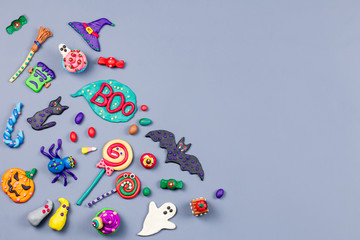 Halloween background with decorations. Black cat, bats, witches hat and broomstick with orange pumpkins. Top view