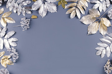 Winter concept flat lay with golden and silver leaves. Christmas frame background