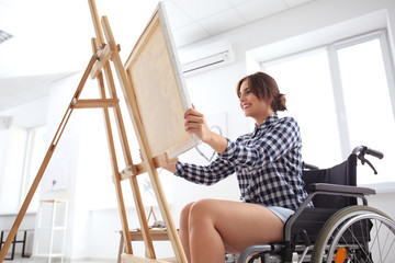 Young female artist in wheelchair painting picture at home