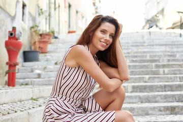 smiling girl sitting on the stairs in the city. Resting girl.
