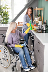 Mature woman in wheelchair cleaning kitchen together with daughter