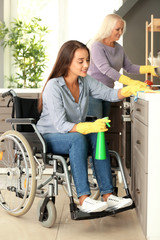Young woman in wheelchair and her mother cleaning kitchen