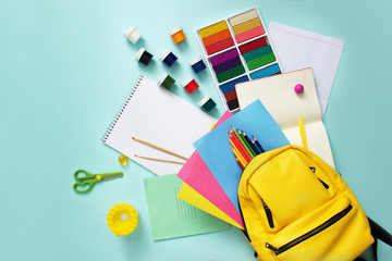 concept School supplies sets and knapsack on blue background. Top view.