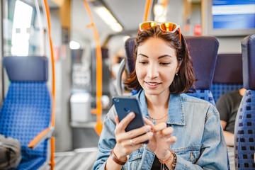 Happy Asian woman using mobile phone app in train