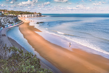 Low tide at Stone Bay, Broadstairs, Kent as summer turns to autumn, a lone surfer walks on the beach and a family on the promenade along side the beach huts and white cliffs. Wall mural