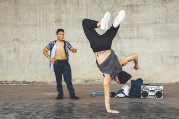 Two mixed race young break dancers training in the street