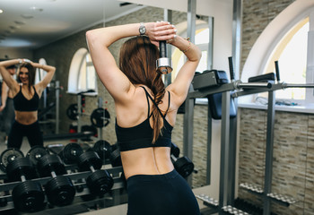 Beautiful girls with long hair is training in the gym with weights. Personal fitness trainer is at work doing exercises for good muscles. Sport motivation healthy lifestyle. Woman body workout.