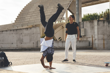 Young hispanic break dancer performing a dance pose surrounded by friends in urban park at sunset