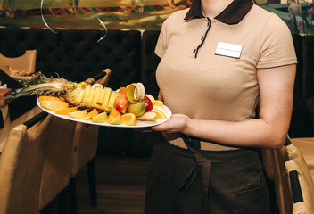 Waitress in beige uniform T-shirt with badge sets the table at the restaurant. Girl is holding a plate with fruit in her hands. Birthday party at the cafe.