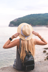 Tuinposter Art Studio back view of woman holding hat and looking at Adriatic sea at Ricardova Glava beach, Budva, Montenegro