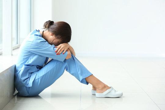 Tired female nurse sitting on floor in hospital