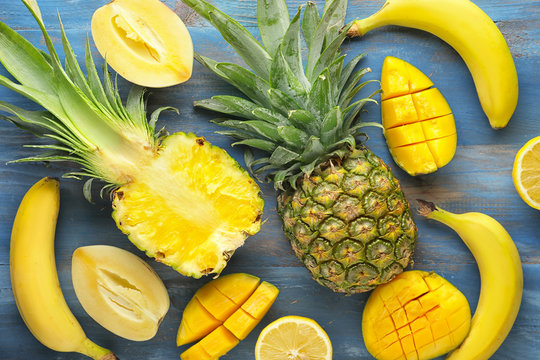 Summer composition with tropical fruits on wooden background