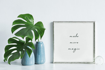 Modern and minimalistic composition of mock up photo frame with green tropical leafs in design vase.  Stylish concept of mockup frame. White backgrounds wall.