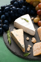 Slate plate with cheese and ripe juicy grapes on color table