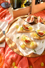 Tasty sandwiches with cheese, grape and fig on wooden board