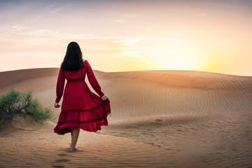 Girl walking in the desert at sunset