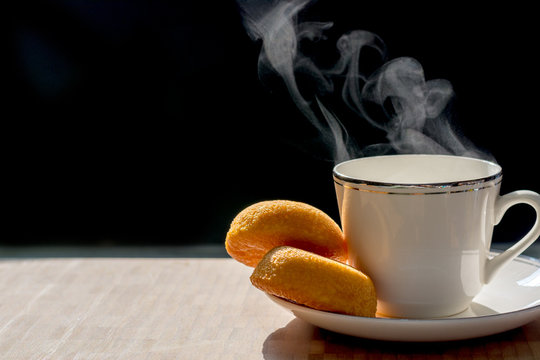 White cup of coffee with smoke and bakery isolated on dark background.