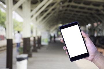 Woman hand holding and showing mobile smart phone with blank white screen on train railway station blurred background. Internet technology concept.