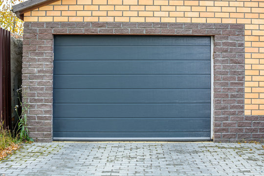 Automatic garage gate. Access to a brick garage for a car with a dark door