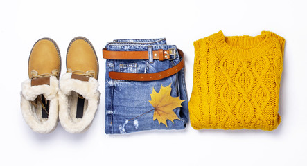 Female orange knitted sweater, blue jeans, boots and autumn leaves on green background top view flat lay. Fashion Lady Clothes Set Trendy Cozy Knit Jumper Autumn accessories Female fashion look