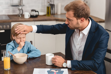 young father checking temperature of son with hand during breakfast