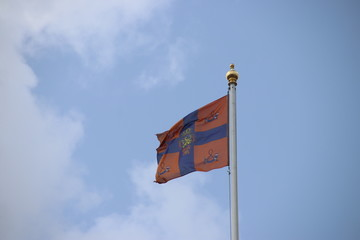 Flag of king Willem-Alexander is waving in the wind on the Noordeinde Palace in the hague, The Netherlands. The flag is symbolizing that the king is in the palace.