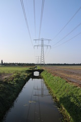 Powerlines reflection on the water of a ditch between the fields in Zevenhuizen, the Netherlands.
