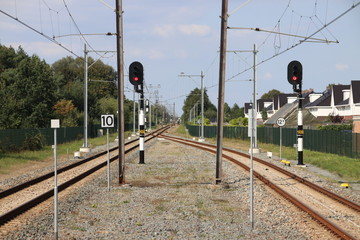 Single track with red signs which splits at the platforms of station Boskoop in the Netherlands for track between Gouda and Alphen