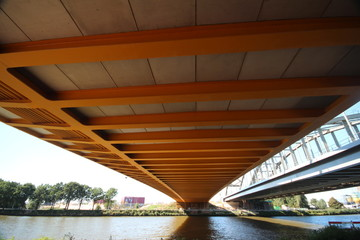 Bright yellow bridge named Hogeweidebrug over the Amsterdam-Rhine canal in Utrecht for traffic and Vleutenspoorbrug which is a trainbridge.