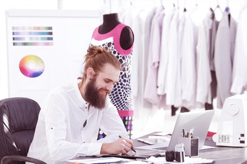 fashion designer uses a graphics tablet to create sketches of clothes