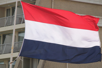 Flag of the Netherlands in the wind on a mast in the red, white and blue color.