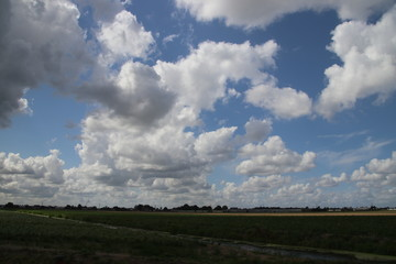 Big cumulus clouds above the meadows and fields of the Zuidplaspolder in the Netherlands