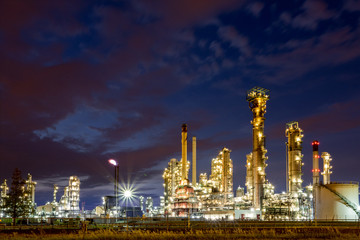 Glittering industrial lights of an oil and gas refinery or petrochemical plant with a blue purple sky background at night