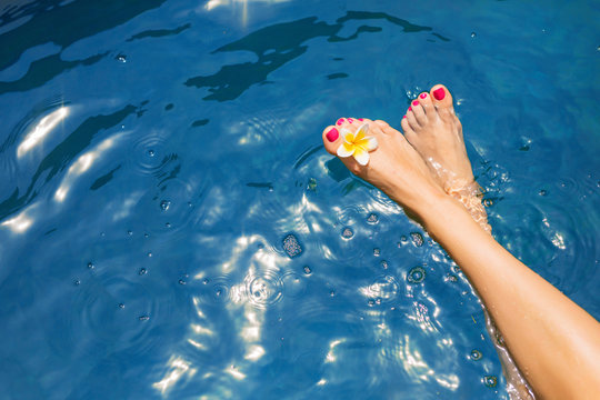 Woman's legs on surface of blue pool water
