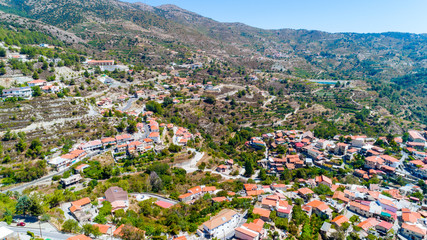 Aerial view of Kyperounda village on Madari, Troodos mountain, Limassol, Cyprus. Bird eye view of traditional ceramic tiled roof houses, countryside, valley and church from above.
