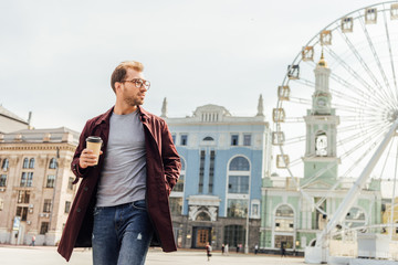 handsome man in autumn outfit walking with disposable coffee cup near observation wheel