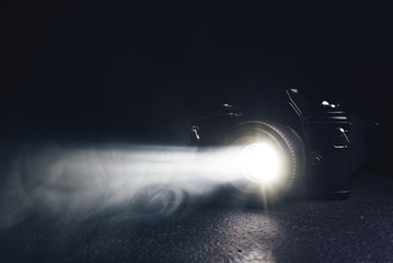 old camera with a ray of light from the lens in the smoke on a black background