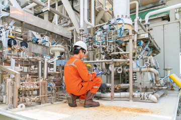 Mechanic operator check lube oil and seal gas systems of gases compressor on offshore central processing platform.