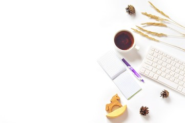 White office table top view/ Cup of tea, purple pen, notepad, computer, dry autumn herbs, pine cones and wooden toy horse. Fall season mood and minimalist aesthetic