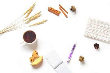 Creative work place/ Flat lay photo office table. Feminine work space. Many objects forming a frame. Cup of tea, purple pen, notepad, computer, dry autumn herbs, pine cones and wooden toy horse