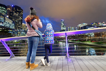 Mother and daughter at night photographing city skyline from beautiful modern bridge