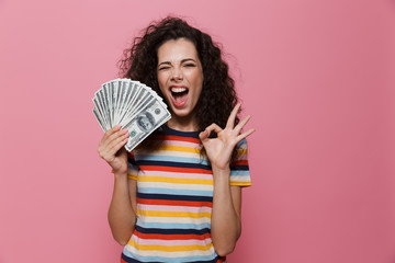 Image of joyous woman 20s with curly hair holding fan of dollar money, isolated over pink background
