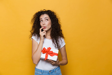 Cute young woman posing isolated over yellow background holding gift box present.