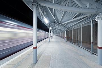 Highspeed train arrives to the station platform at night time.