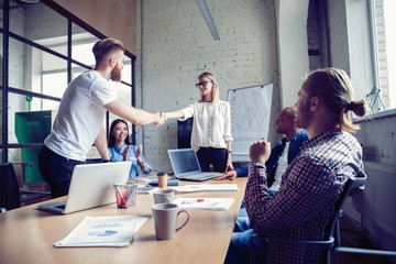 New business partners. Young modern colleagues in smart casual wear shaking hands and smiling while sitting in the creative office.