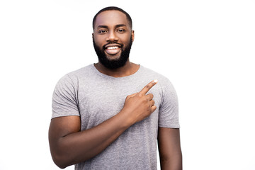 Positive black African American male with happy calm emotion, being glad to be praised or achieve goals, advertizes something, points with index finger at copy space of white studio background.