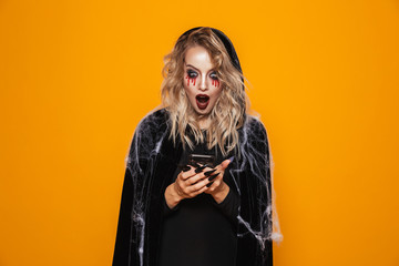 Attractive wizard woman wearing black costume and halloween makeup holding mobile phone, isolated over yellow background Fototapete