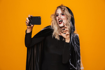 Caucasian woman wearing black costume and halloween makeup taking selfie photo on mobile phone, isolated over yellow background