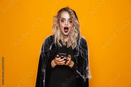 Blond woman wearing black costume and halloween makeup holding mobile phone, isolated over yellow background
