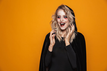Photo of woman wizard wearing black costume and halloween makeup looking at camera, isolated over yellow background